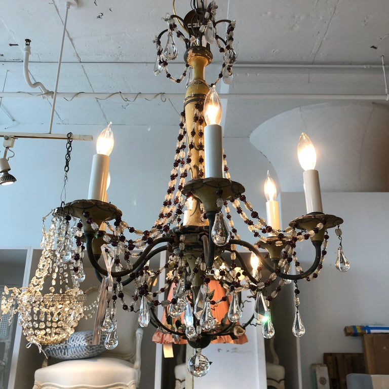 A six arm iron & wooden chandelier with decorative green & mustard paint. Crystal drops and amethyst & clear beading.