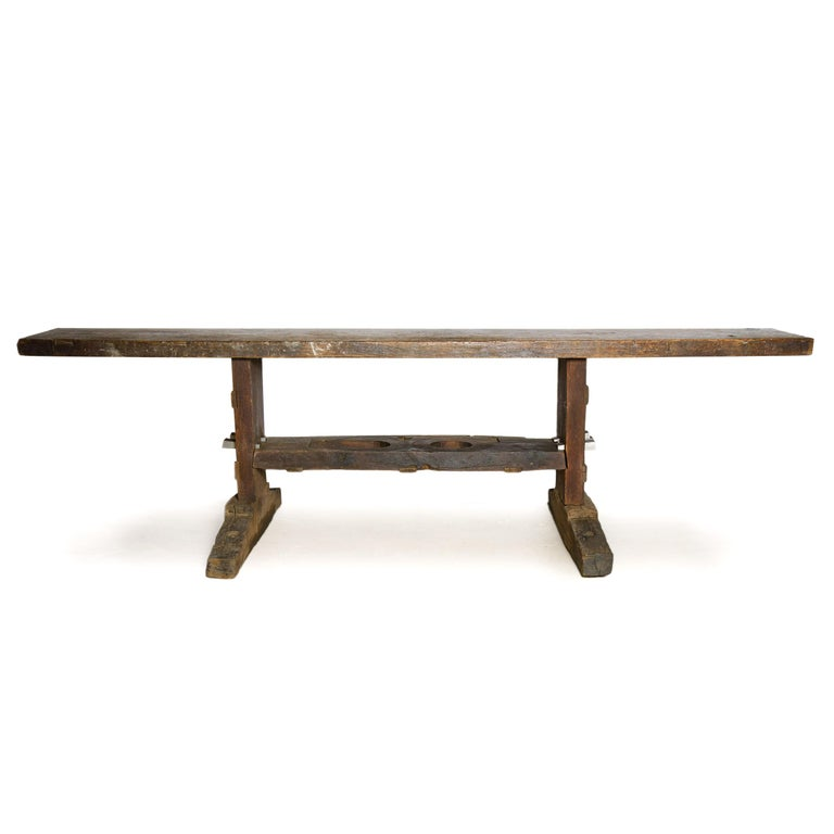 Substantial, antique, solid oak work bench executed in the traditional form of a shoe foot trestle table with its wide lower shelf doubling as a strengthening element tenoned in to both side supports. Neither a commercial or serial production piece,