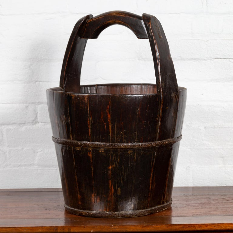 A Chinese rustic wooden bucket from the 19th century, with large curving handle. Born in Southern China during the 19th century, this wooden bucket charms our eyes with its nice proportions and dark patina. Featuring a cylindrical tapering body