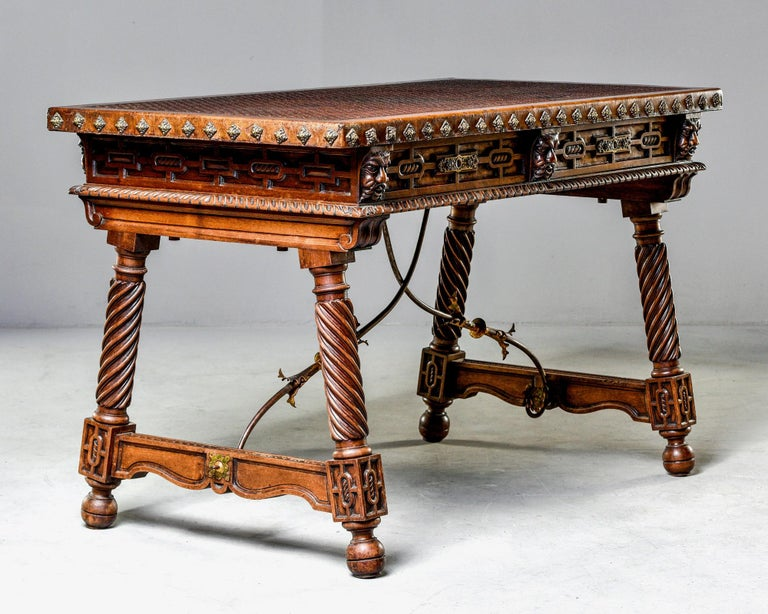 Spanish library or writing table features a new, embossed leather top, decorative brass nail head studs on the desktop edges, carved faces on the apron and two functional locking drawers, circa 1870s. Legs and supports all have carved details and