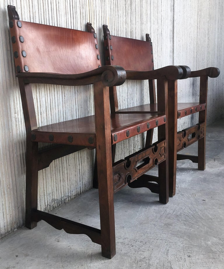 Pair of Spanish colonial style armchairs, having leather both seats and backs, and brass nailheads.  Price per item.