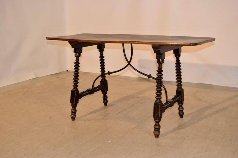 19th century table made from walnut and elm. The top is wonderfully grained curly elm, following down to a base made from walnut with a nicely turned spool shaped legs, joined by matching stretchers and braced together in the centre of the table