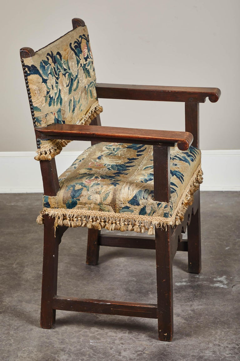 A 19th century Spanish walnut armchair. Beautiful patina. Upholstered in a tapestry with a tassel trim that circles around the seat and lower back. Nailheads decorate the top and sides of the back. Embroidered fabric as seat and back upholstery.