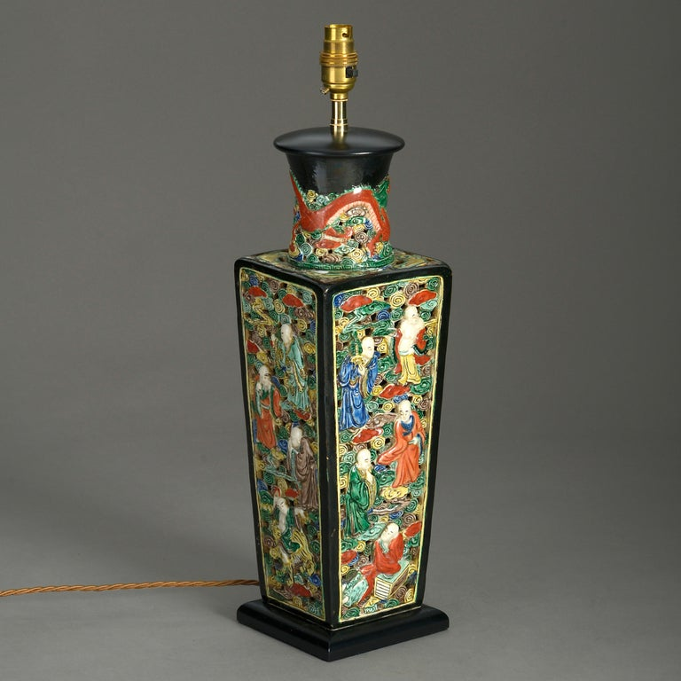 A mid-19th century polychrome vase of square tapering form, the black glazed neck with dragon motifs, the sides intricately worked with figurative scenes upon a pierced scrolling ground. Now mounted as a table lamp.  Wired for electric lighting