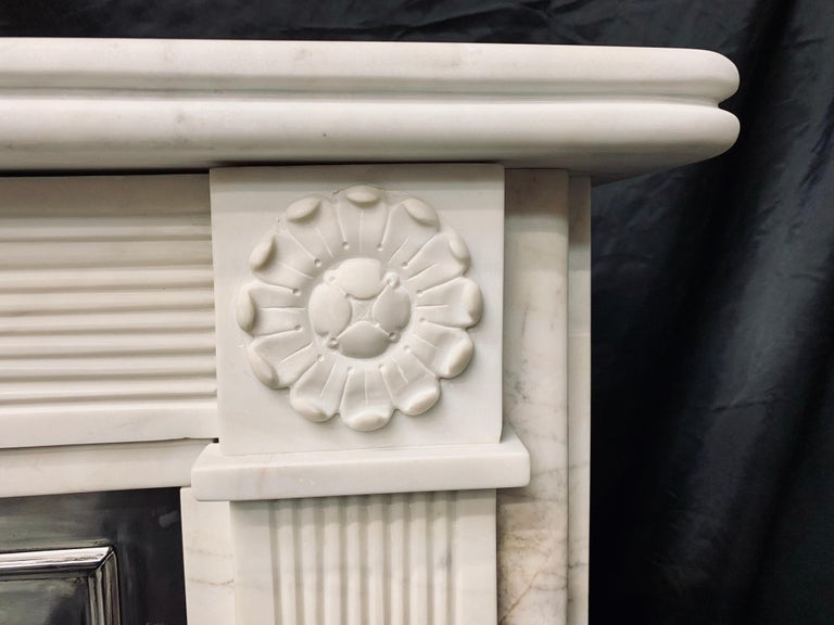 A small and attractive 19th century Regency style lightly veined statuary marble fireplace surround, a reeded shelf sits above a fine reeded stepped frieze, flanked by capitols with well carved rosettes supported by fine reeded jambs all supported