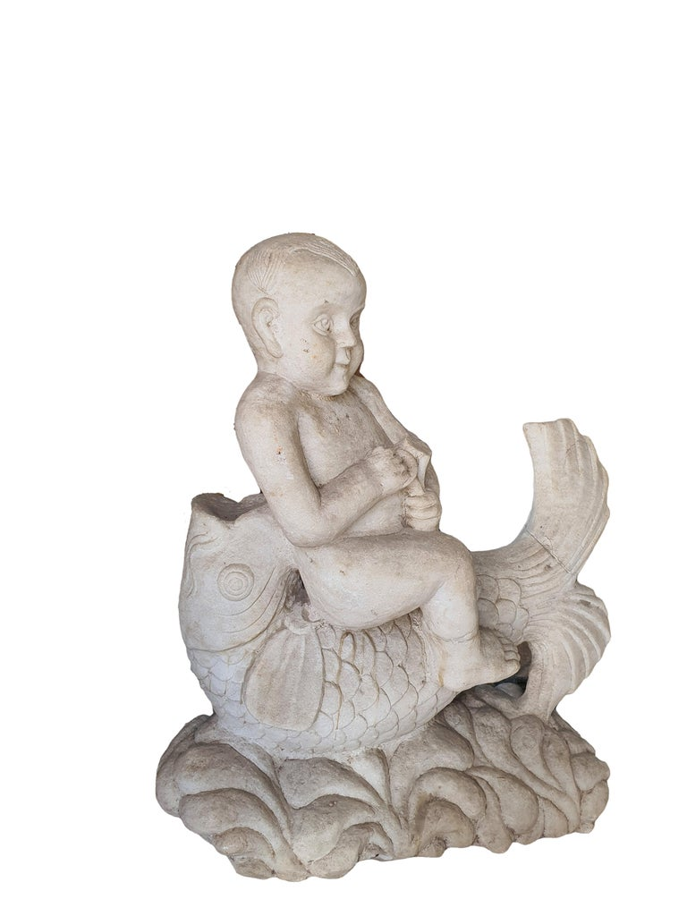 Elegant white statuary marble sculpture, carved from a single block of marble, depicting a cherub sitting on a sea fish. Finely carved in every detail.