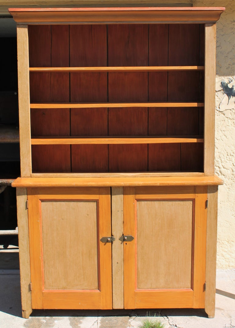 This fine original painted open pewter cupboard is in fine condition with lots of space for your collection of antique dishes or pewter collection. The cream or tan finish with bittersweet trim doors has the original hardware as well. The backboards