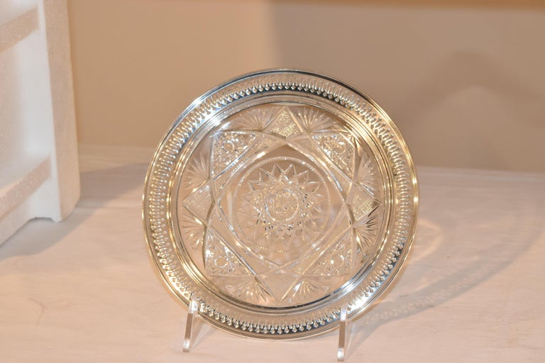19th century cut glass plate surrounded by a rim of sterling silver, which has a molded edge and piercing. Stamped on the back RW&S, which is R. Wallace and Sons.