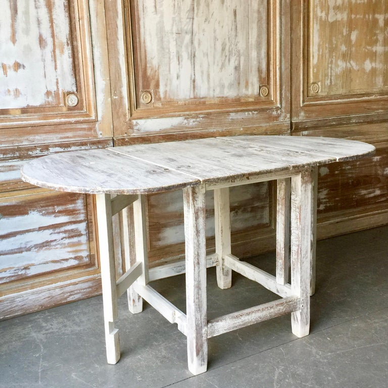Charming 19th century Swedish painted pine gateleg table with rounded drop-leaves.