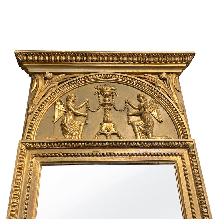 An antique large late Swedish Gustavian wall mirror with a gilded frame and original glass, enhanced by detailed wood carvings with two angles, in good condition. Wear consistent with age and use. Circa 1800 Stockholm, Sweden, Scandinavia.