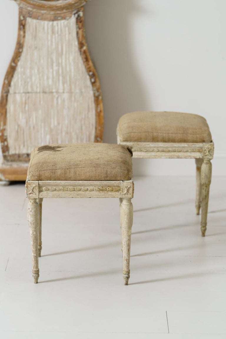 A pair of Swedish period Gustavian stools from the 19th century wearing their original linen. There are carved bell flowers on the seat frame with wheat sheaths on the corner posts. Manor house quality stools.