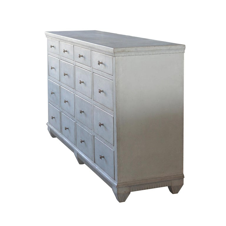 A unique Swedish apothecary cabinet made of grey painted pinewood, composed with sixteen, richly carved drawers. The hand carved pharmacy desk is in good condition, detailed in the neoclassical Greek style with their original brass hardware,