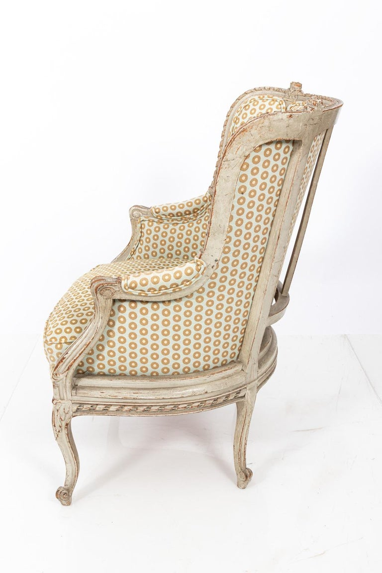 Swedish Gustavian style bergère armchair with distressed finish and tub back surrounded by carved flowers. Please note of wear consistent with age, circa 19th century.