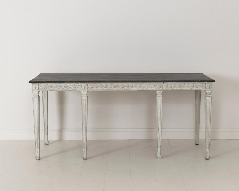 Swedish late Gustavian console table from the 19th century with hand painted black porphyry top. The apron is decorated with bell flowers and the leg posts with lion heads. This beautifully classic table is raised upon square tapered and channeled