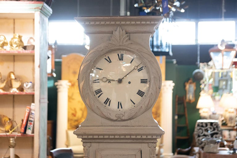 Swedish Gustavian style painted tall case clock in working condition, circa 19th century. The case is detailed with dentil trim, carved folliage framing the face, and composite columns on the body. The piece chimes every hour. Please note of wear