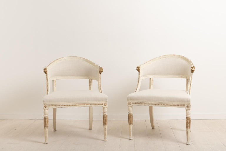 Set of two barrel back armchairs with renovated seats. The armchairs have renovated padding and have been upholstered with new fabric. Manufactured in northern Sweden circa 1880 the chairs are made in the Gustavian style, a style popular in Sweden