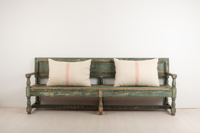 Swedish sofa bench in painted pine. The bench is Folk Art and made in Baroque style. The green paint is original and naturally distressed due to age and use. Originally from northern Sweden and made circa 1830. The bench is quite wide at just over 2