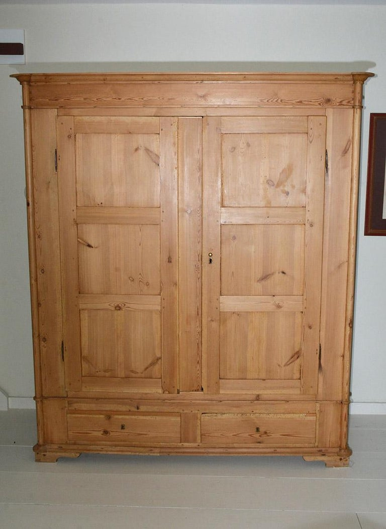 Rustic country style pine armoire has 2 large recessed panel doors, 2 bottom drawers and several shelves. The wardrobe is currently being used as television entertainment cabinet but can easily be converted to storing clothes or other effects. Great