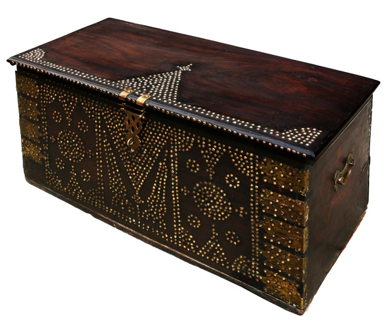 A stunning rare 19th century Zanzibar or Bombay chest composed of six thick slabs of teak wood. The exterior of the trunk is outfitted with brass sheets and studs in geometric patterns, particularly pyramidal shapes mounted by crosses, representing