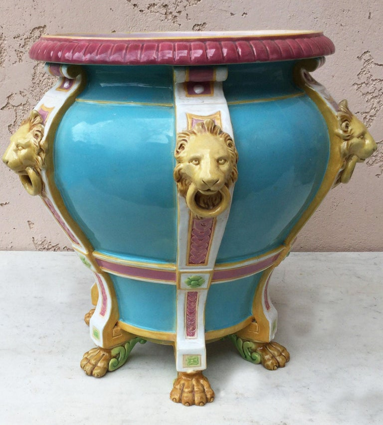 19th century aqua turquoise Minton jardiniere with six pilasters applied with lion mask and ring handles and stands on paw feet.