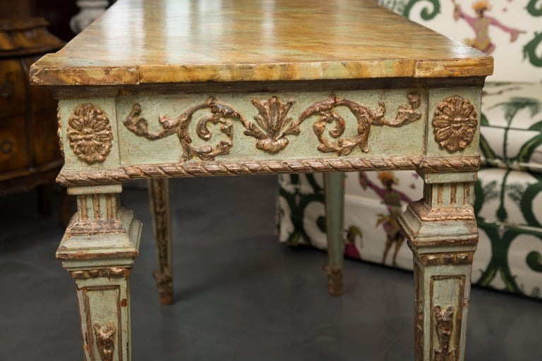 Ultra 'old world' sophistication radiates from this magnificent light green painted and parcel gilt rectangular console table. The table has a faux marble top over a gilt-embossed freize and supported by square tapering legs with a similar motif.