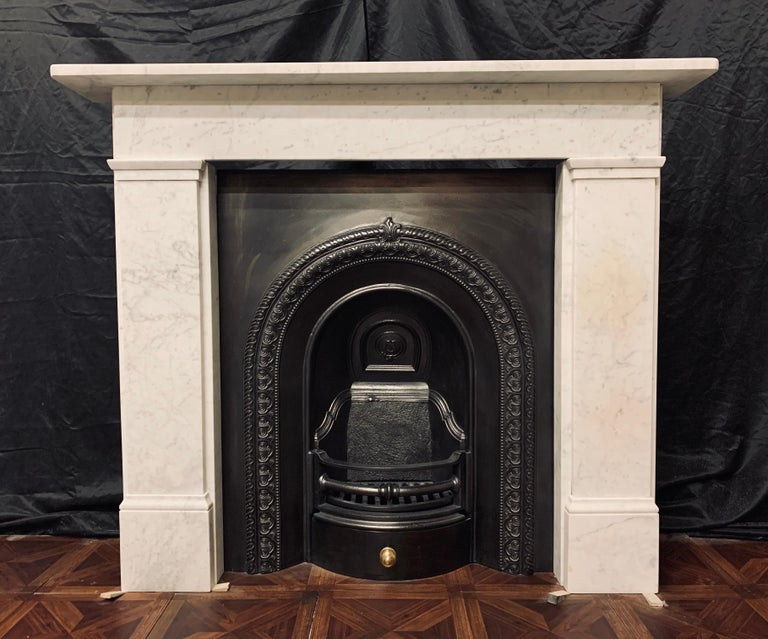 A small and attractive 19th century Victorian marble fireplace surround of simple form, a square shelf sits above a plain straight through frieze, supported by stepped jambs with block and capping moulding to the frieze line, all resting on moulded