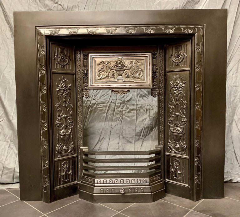 A charming and ornate 19th century Victorian cast iron fireplace insert with exquisitely cast side panels and a polished fire hood showing a central urn flanked by Cornucopia and bell flowers and swags. A generous sized piece that is stamped with a