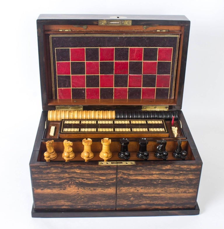 This is a wonderful antique Victorian coromandel games compendium, circa 1860 in date.  The hinged lid reveals fitted compartments, the interior with two lift-out trays fitted with boxwood and ebony draft pieces, a cribbage board, bone dominoes,