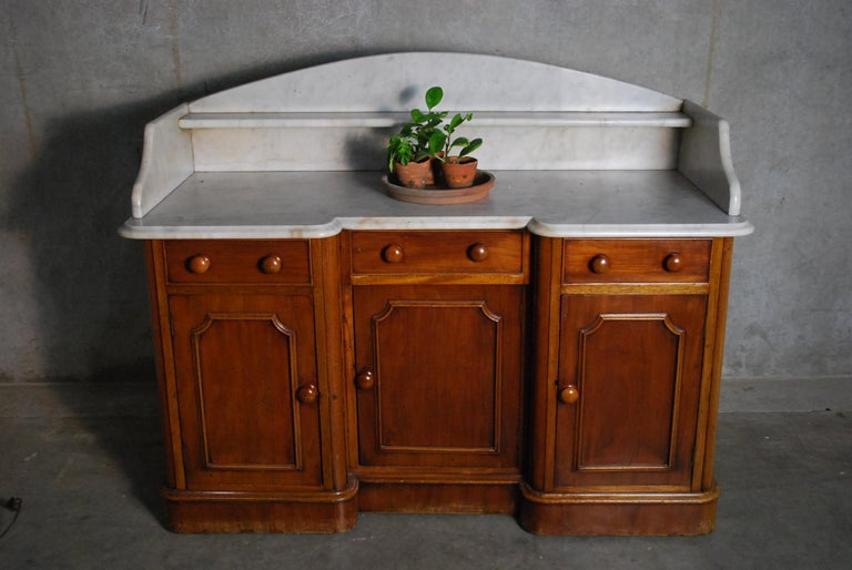 Beautiful untouched piece with multiple doors, unbroken marble top, in old finish solid mahogany.