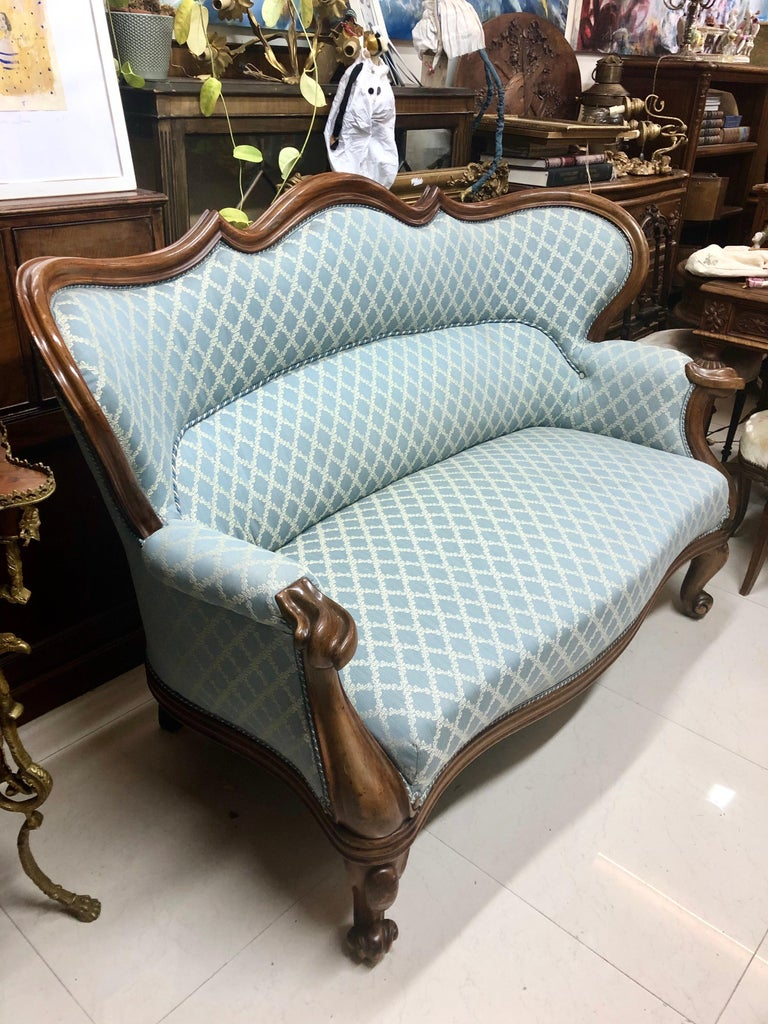 19th century Victorian mahogany two-seat sofa with a moulded show frame and serpentine wing back, on cabriole front legs and scroll toes. Upholstery in light blue fabric. Great condition.