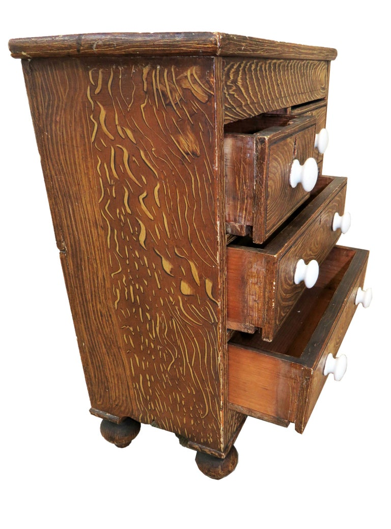 A very attractive and charming late 19th century Victorian painted pine miniature chest having two short drawers and two long drawers with original porcelain knobs raised on elegant turned feet  (Almost certainly made by an apprentice to try