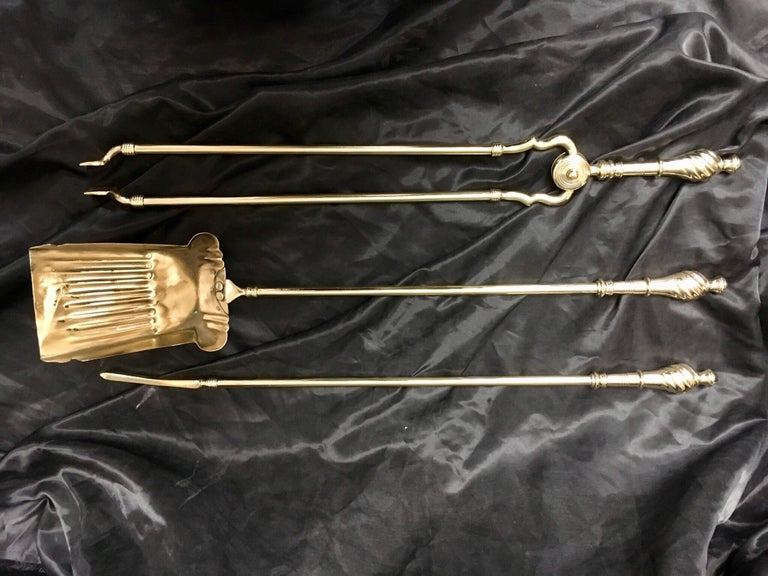 A set of three Victorian 19th century brass fire Irons consisting of a poker, a shovel, and a pair of tongs, each with a spiral and pommel finial handle.  English, circa 1890.