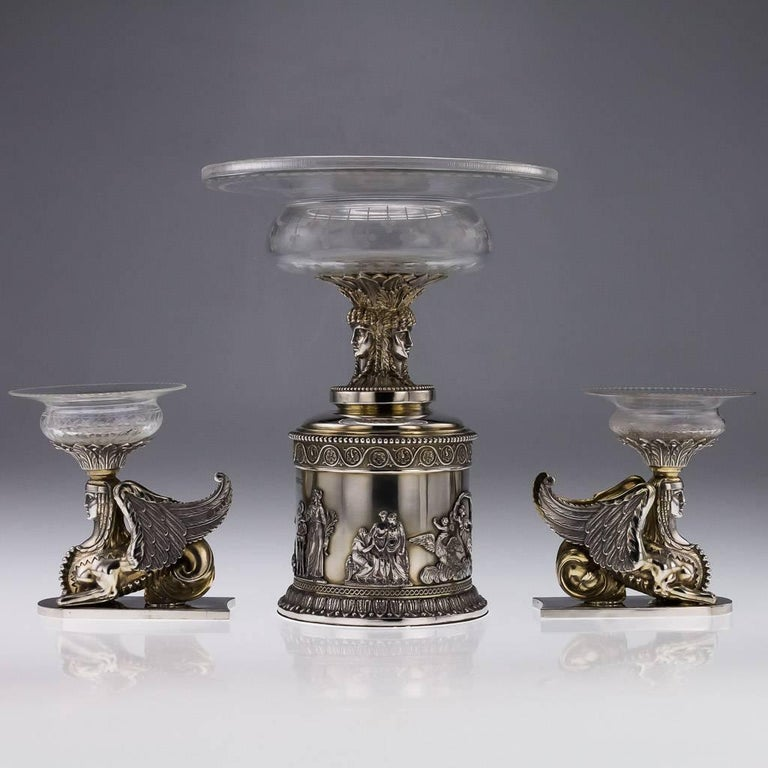 Antique 19th century rare and magnificent Victorian solid silver three-piece table garniture, the cylindrical central piece applied with a cast Neoclassical frieze depicting mythological figures, surmounted by a triple-headed Greek goddess, the