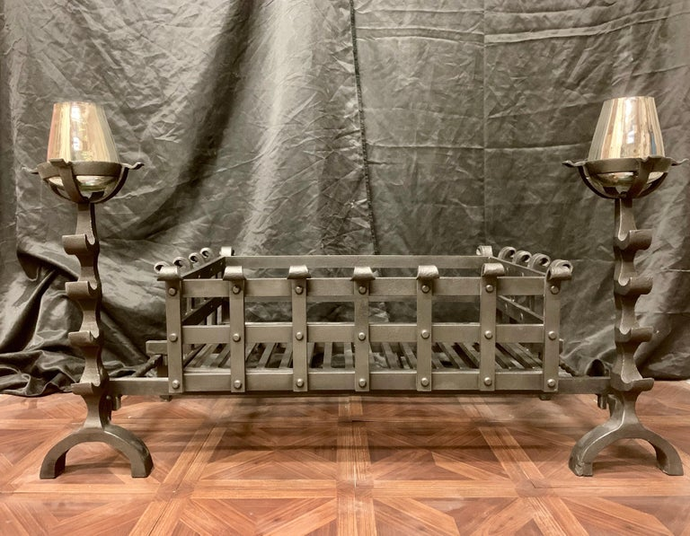 A very large 19th century Victorian style wrought iron fireplace grate, a pair of tall fire dogs with tool rests and circular cup warming holders play host to a very large riveted central fire basket with a generous burning area- scrolls to