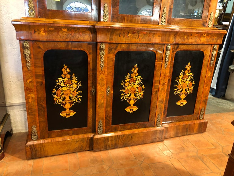 English bookcase with three doors, from the Victorian period, circa 1860, in walnut and inlaid with fruit woods. Applications in gilded bronze on the uprights of the doors. To be restored but in excellent condition.