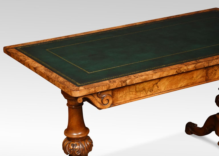 19th century walnut library table, the large rectangular top with rounded corners having tooled inset leather writing surface. The frieze is fitted with two freeze drawers supported on twin carved uprights. All raised up on cabriole legs terminating
