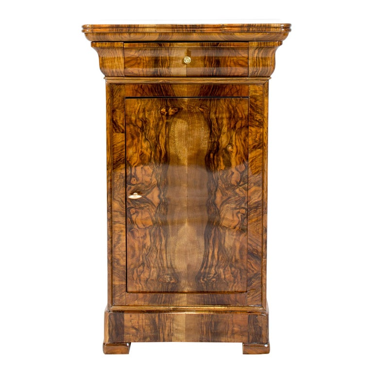 Beautiful Biedermeier walnut veneer nightstand or pillar cabinet from Germany. Back and shelf is made of spruce wood as usual. The opening handles are made of brass. There is a drawer at the top and a door below. The furniture is in a very good,