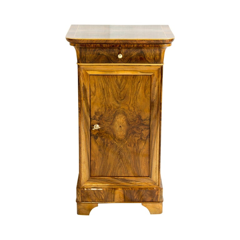 Beautiful Biedermeier bedside table or side cabinet in walnut veneer from Germany. The top is finished with mahogany edge and maple strips. The back wall and the shelf are made of spruce wood as usual. The opening handles are made of brass. There is