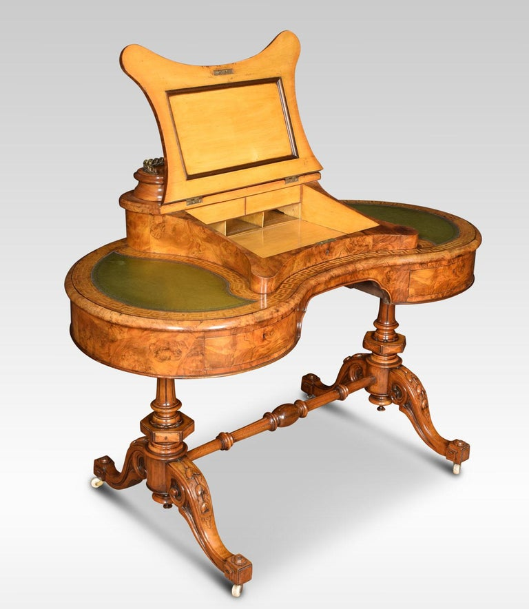 Walnut writing desk, of kidney shape, profusely inlaid in satinwood with a Greek key design, the top with a central raised superstructure, with cast brass gallery, above a hinged sloping surface with inset green leather, enclosing an arrangement of