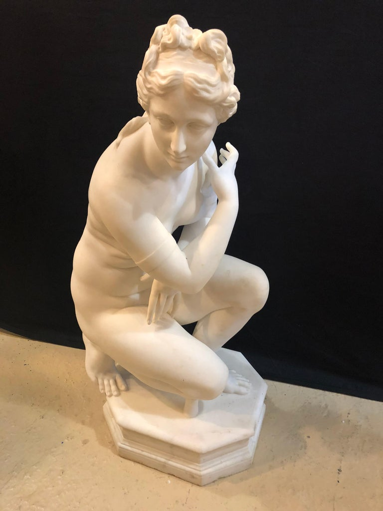 A 19th century white Carrara marble of a nude life sized figure kneeling. She is everything one could dream of. This fantastic life-sized semi-nude maiden is trying desperately to hide her ample breasts while kneeling upon a rock. The detail is