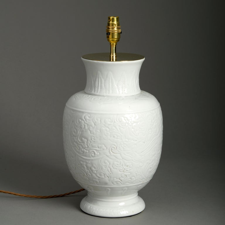 A late 19th century white glazed porcelain vase, the body with incised decoration.  Now wired as a table lamp.  Dimensions refer to vase only and do not include electrical components.  This lamp has been tested to UK safety standards and can