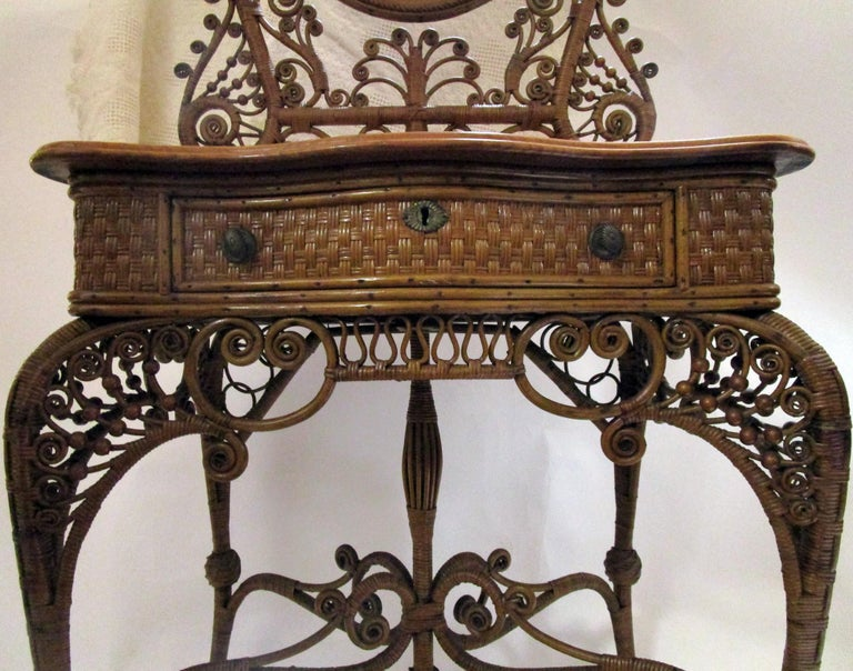 Of all the fanciful pieces of American wicker ever produced, this is the top of the line for advanced collectors. To find one in great condition and in natural stain is very unusual indeed. This sumptuous dressing stand vanity was featured in the