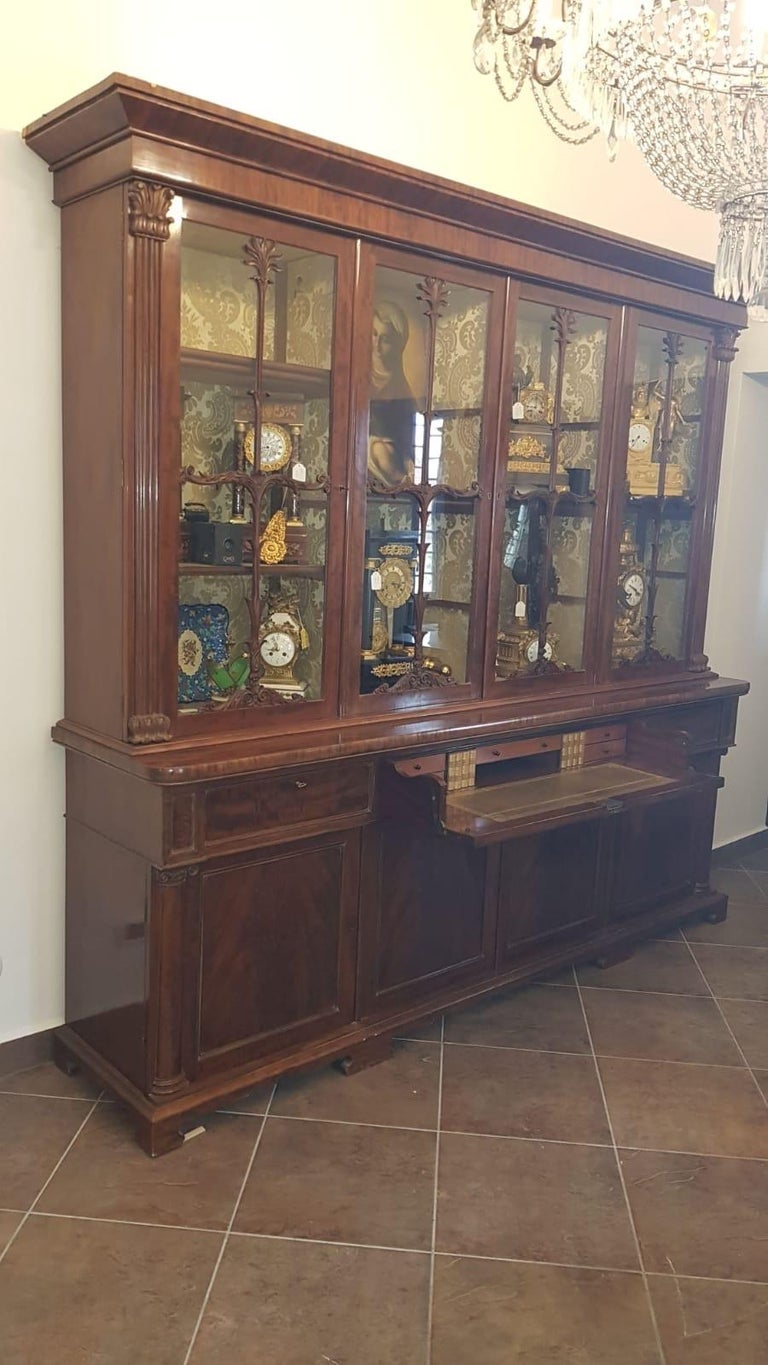 Irish bookcase in mahogany and mahogany feather, with carved capitals on the uprights of the doors, central flap drawer with internal drawers. Furniture of extreme beauty and proportions that make it a light piece of furniture, not as heavy as some