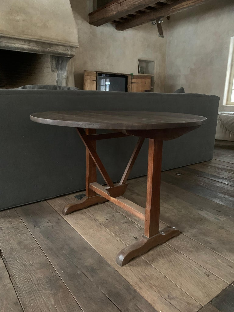 A good 19th century French Winetable. The oak top folds on the elm base. These Vigneron tables were and are used on the French countryside as occasional tables in winecellars and on the field. Often made by farmers in the wintertime they are