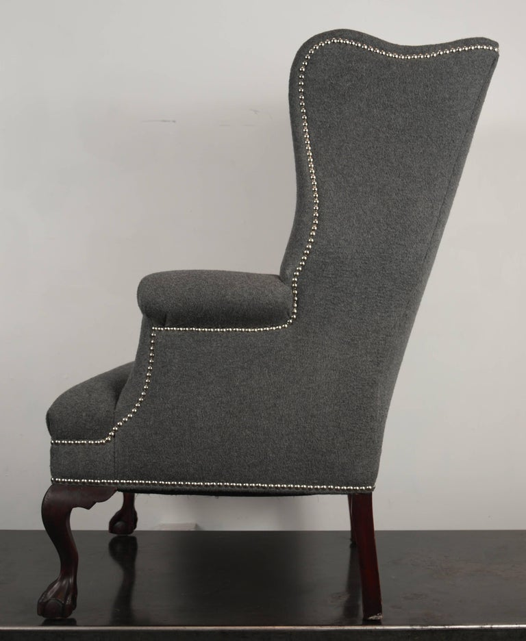 Fully restored 19th century stylized wingback chairs upholstered in gray wool and cashmere fabric and outlined in nickel nailhead trim.