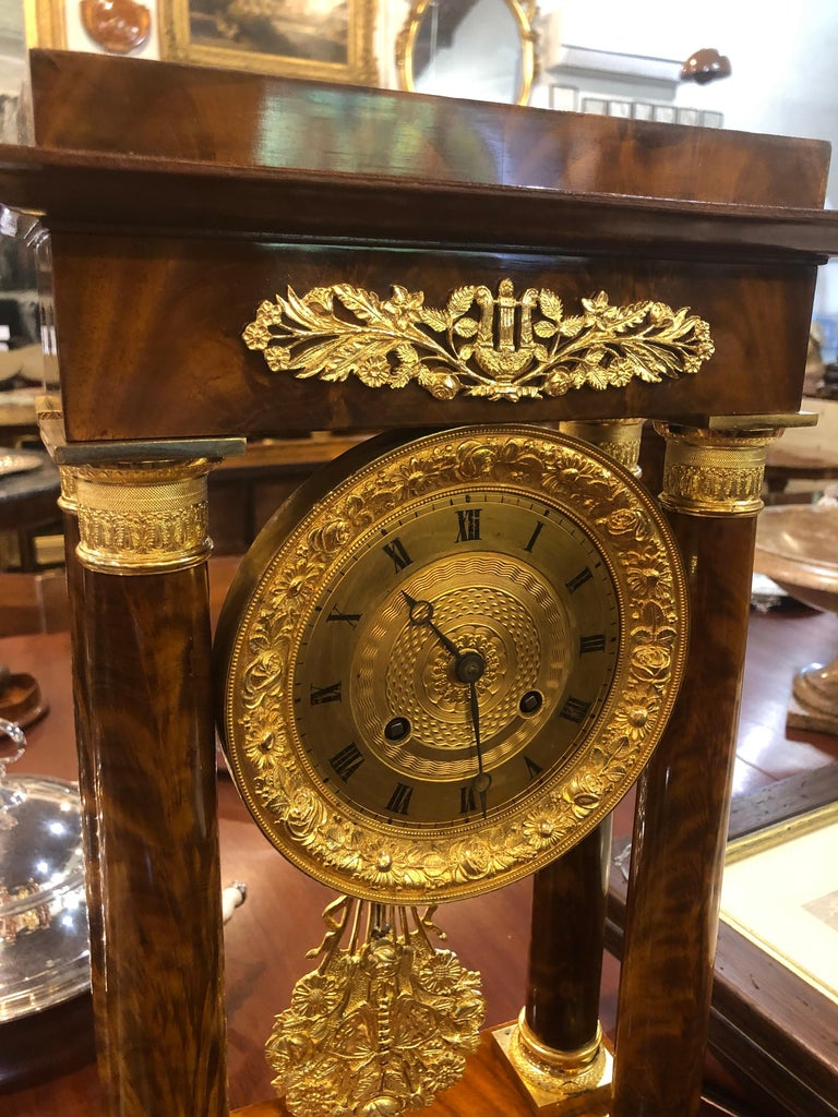 French portal clock with four columns, in flamed mahogany, the wooden part restored, only the mechanism needs to be restored. Fantastic bronzes still with original gilding, Fine chisel execution, beautiful work on the pendulum which represents a