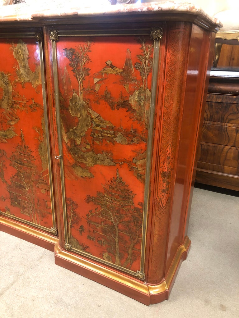 French sideboard, Napoleon III period, circa 1860, lacquered in red with gold Chinoiserie designs, original bronzes framing the three doors, the sideboard is moved on the sides, the marble has a restoration. Inside (completely in solid oak like the