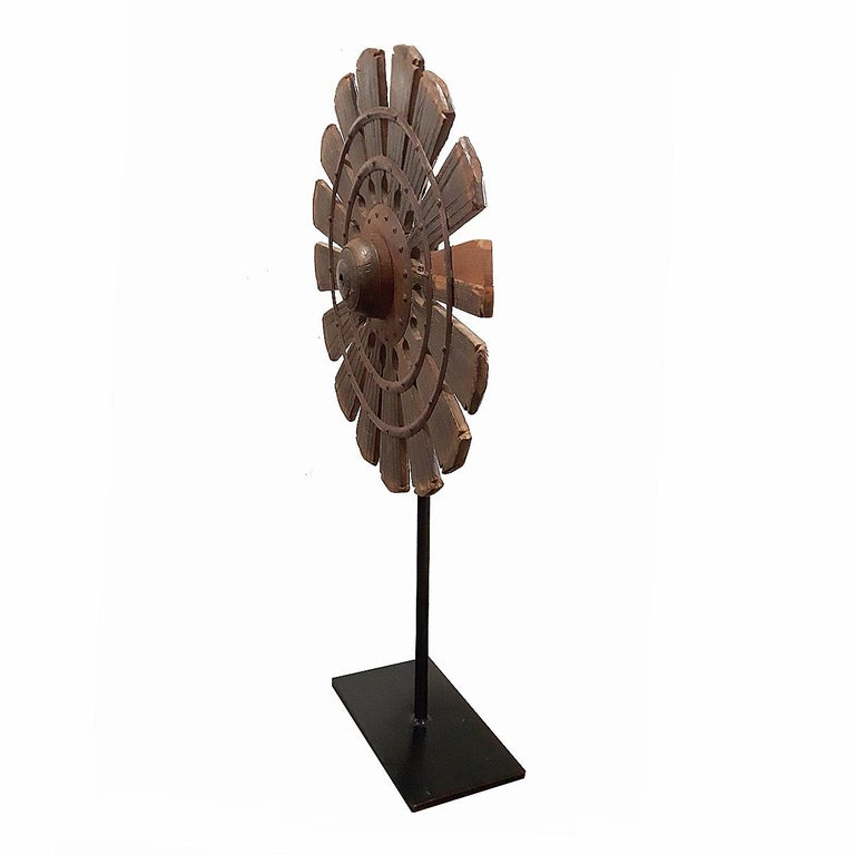 Once a part of an antique thread spinning machine, this spinning wheel was hand carved out of a single piece of teak wood, with metal center and rivets. Mounted on a black metal stand.