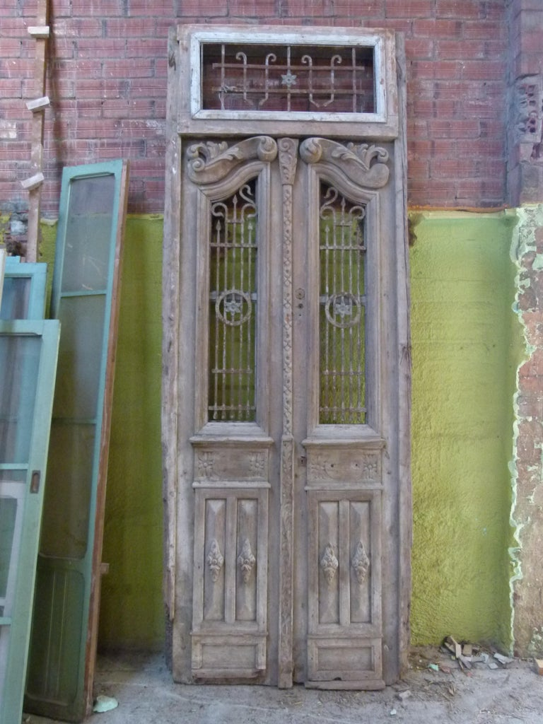 19th century wooden double front door with patina in art nouveau style from Catalonien, Spain.  Carved wood and cast iron typical from this period. The door is framed and working but needs some restoration as some parts are damaged. The original