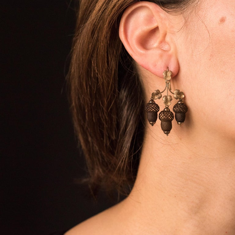 Earrings in 14 karats yellow gold. Each ear pendant is made of a chiselled gold oak leaf that holds a pattern also made of 3 oak leaves that each hold 3 glans made of brown hair and ending with a golden cap. The fastening system is a